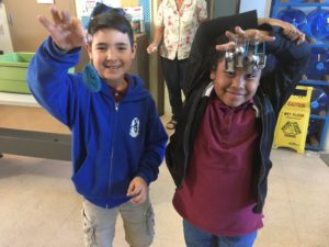 Two kids hold up crafts made from old bike parts