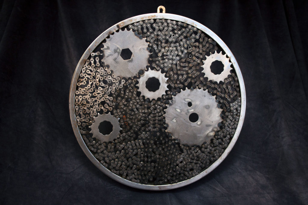 Round hanging metal sculpture with large circle gears inside