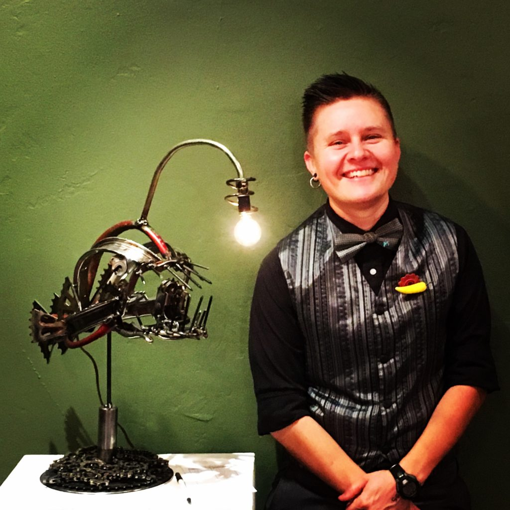 Photo of a person standing next to a lamp in the shape of an angler fish.