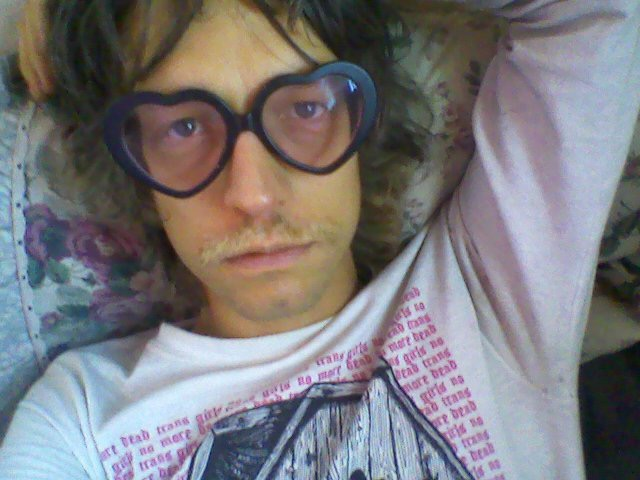 Photo of a person lying down, looking up at camera, wearing heart sunglasses