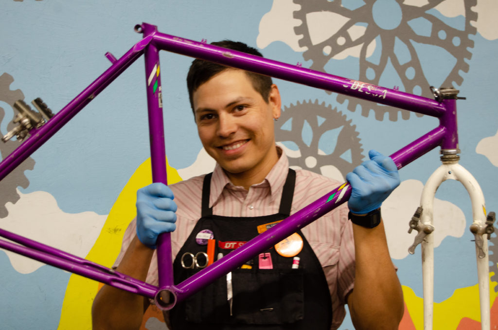 Photo of a person smiling and looking through a bike frame