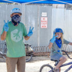 An adult and child give a peace sign with their fingers outside the BICAS shop.