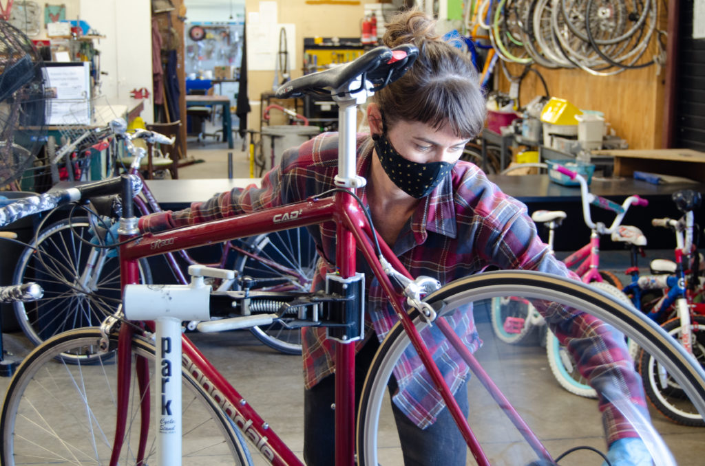 BICAS staff member works on a bike while wearing a facemask