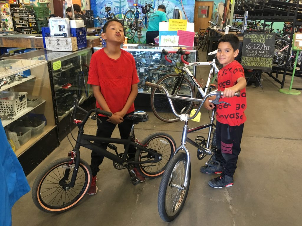 Two kids, approximately ages 8-10, stand proudly with bicycles they have just earned.