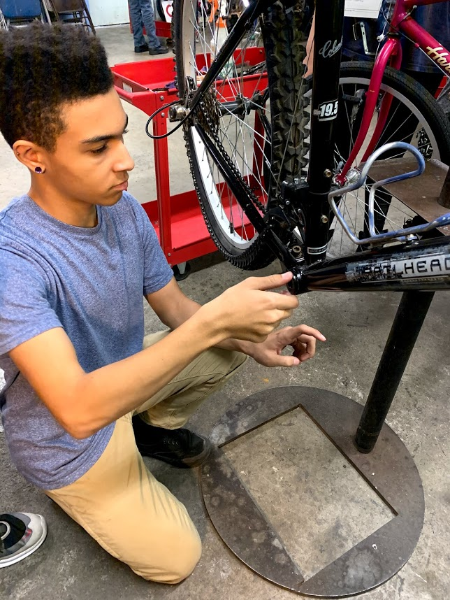 A teenage student works on a bicycle bottom bracket.